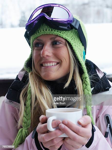 young woman in ski-wear with cup of hot chocolate, close-up, portrait