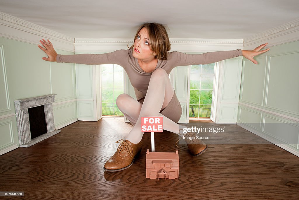Young woman in small house with model of house for sale : Stock Photo