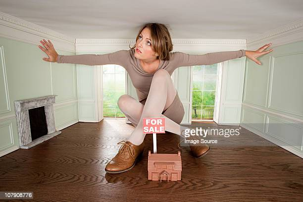 Young woman in small house with model of house for sale