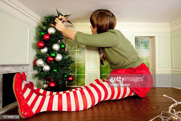 Young woman in small room decorating christmas tree