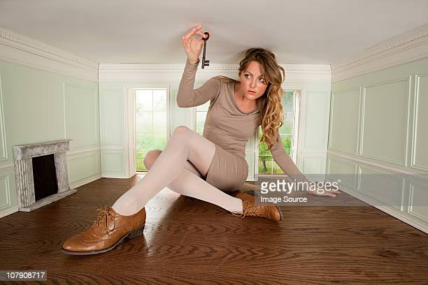 Young woman in small room holding a key