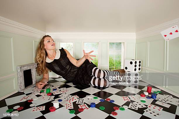 Young woman in small room throwing playing card