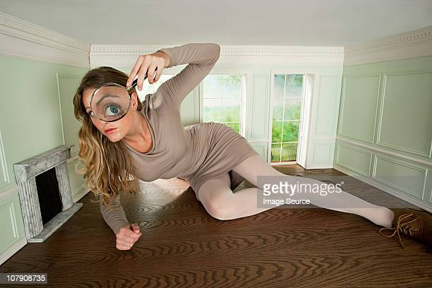 young woman in small room with magnifying glass - big eyes stock photos and pictures