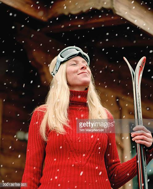 Young woman in snow holding skis, eyes closed