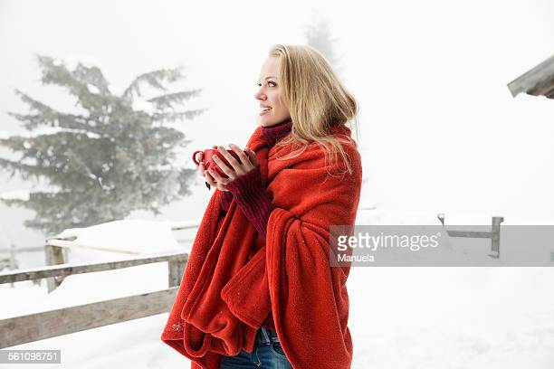 young woman in snowy mist wrapped in red blanket drinking coffee - warme dranken stockfoto's en -beelden