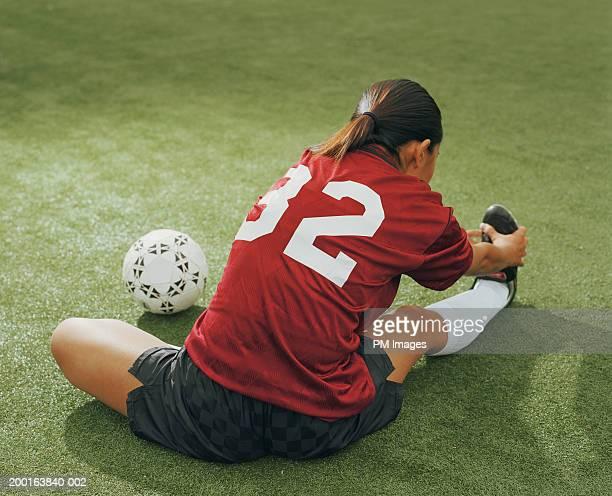 young woman in soccer outfit doing stretching exercises, rear view - precalentamiento fotografías e imágenes de stock