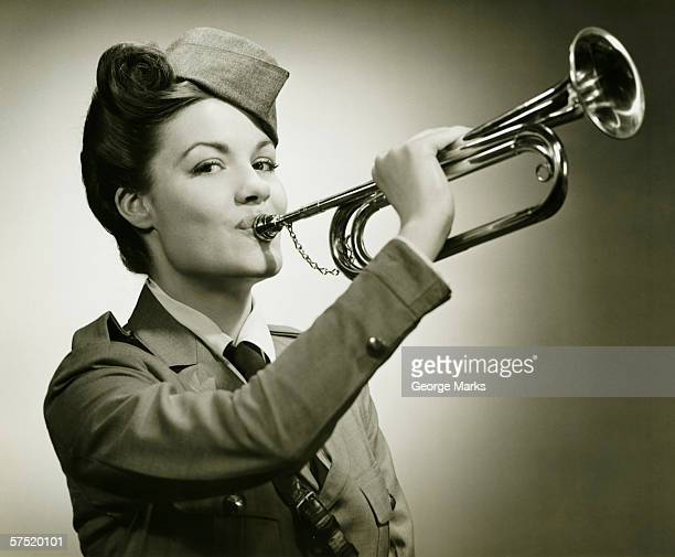 young woman in soldiers uniform playing on bugle, (b&w), portrait - bugle stock pictures, royalty-free photos & images