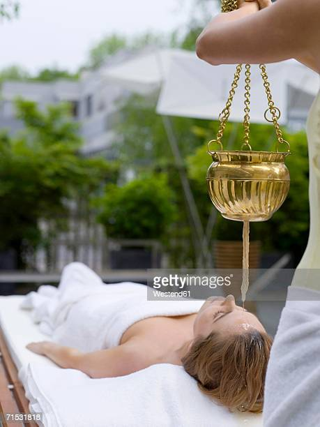 Young woman in spa with oil being poured on forehead