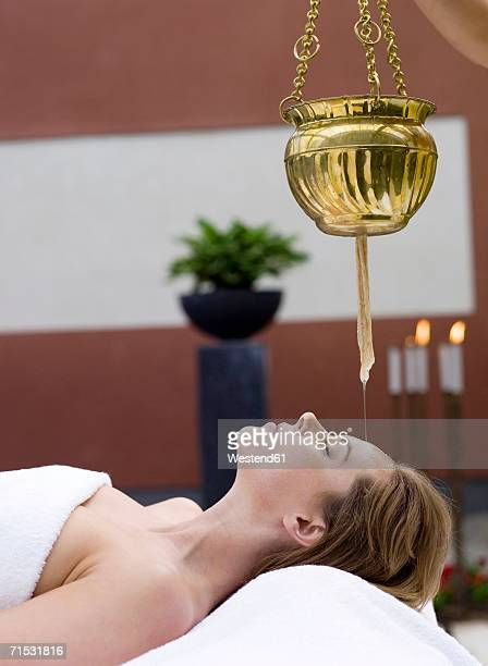 Young woman in spa with oil being poured on forehead, side view