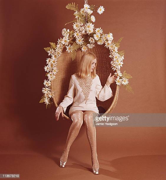 A young woman in spangly tights sits in a flowercovered hanging seat circa 1970