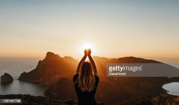 young woman in spiritual pose holding the light - balearic islands stock pictures, royalty-free photos & images
