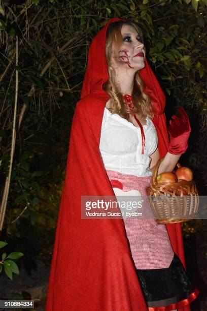 Young Woman In Spooky Make-Up Carrying Basket While Standing By Trees At Night