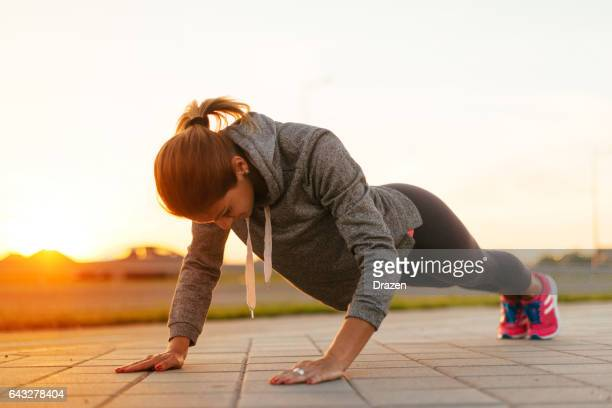 Young woman in sport clothing having outdoor training on hot summer day.