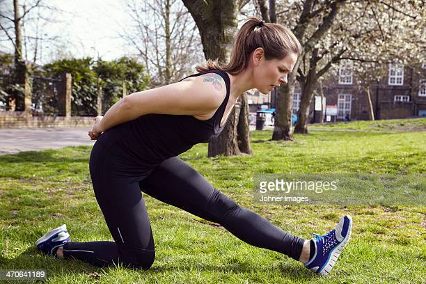 Young woman in sports clothes stretching in park
