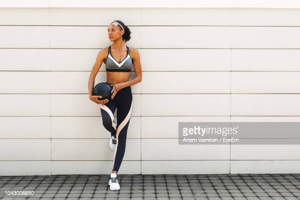 young woman in sports clothing holding ball while leaning on white wall - sports bra stock pictures, royalty-free photos & images