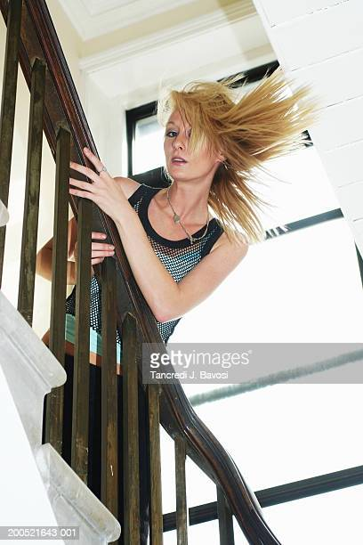 young woman in staircase with windswept hair, portrait, low angle view - bavosi stock photos and pictures