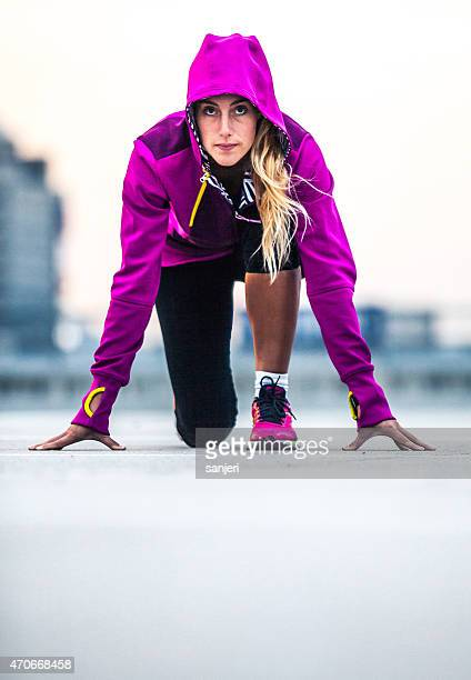 Young woman in start position for running