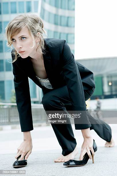 Young woman in starting position on pavement, hands in shoes