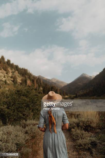 young woman in stetson and maxi dress strolling on rural valley dirt track, rear view, mineral king, california, usa - long dress stock pictures, royalty-free photos & images