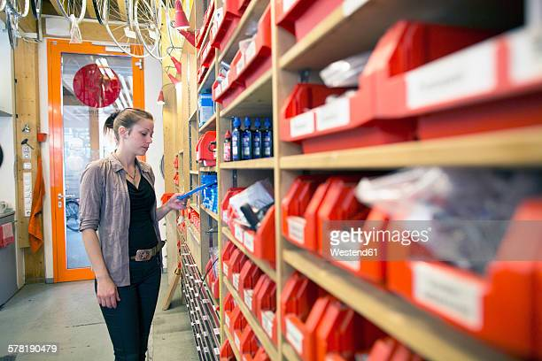 Young woman in storeroom of a bicycle repair shop