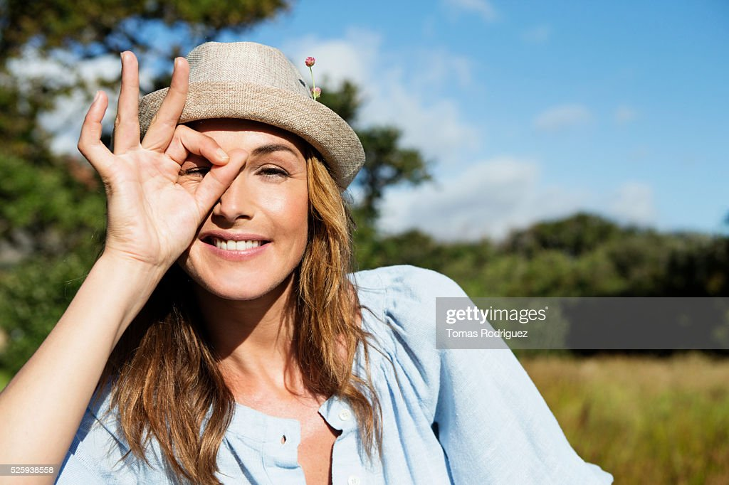 Young woman in straw hat making funny face : Stock Photo