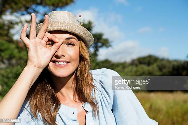 Young woman in straw hat making funny face