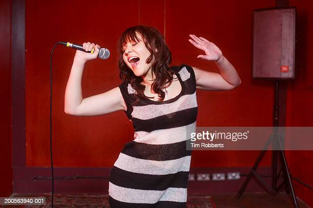 Young woman in striped dress singing into microphone on stage