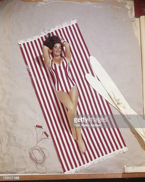 Young woman in striped swimwear lying on striped blanket, smiling, portrait