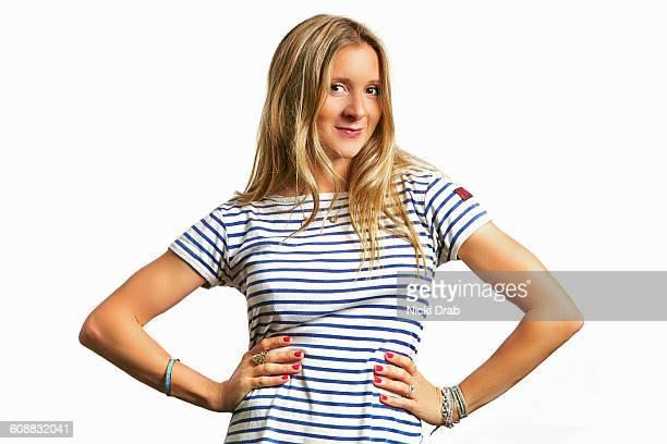 Young woman in stripy tshirt smiling hands on hips