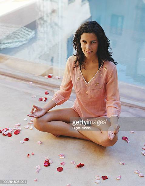 Young woman in sukhasana pose by swimming pool, smiling, portrait