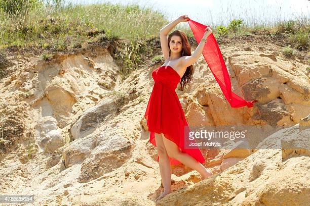 Giovane donna in abito estivo ballare con bandiera tra sandstones