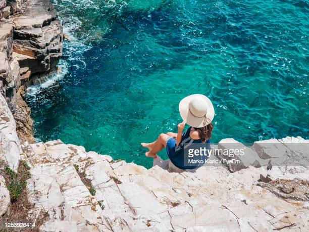 young woman in summer outfit on cliff above sea. - イストリア半島 プーラ ストックフォトと画像