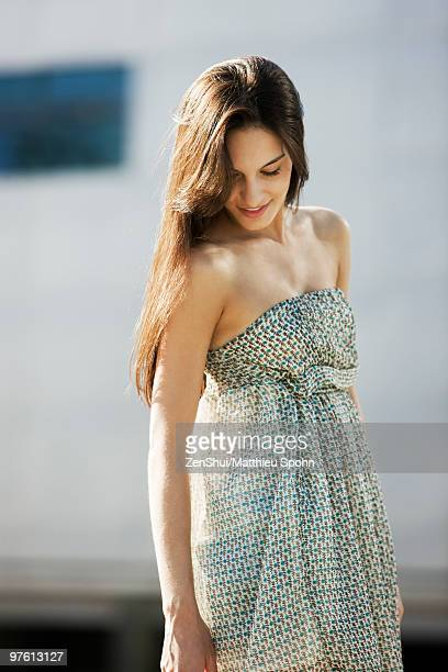 Young woman in sundress standing outdoors, looking down