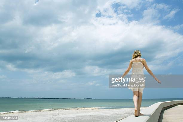 Young woman in sundress walking along low wall at the beach, arms out, rear view