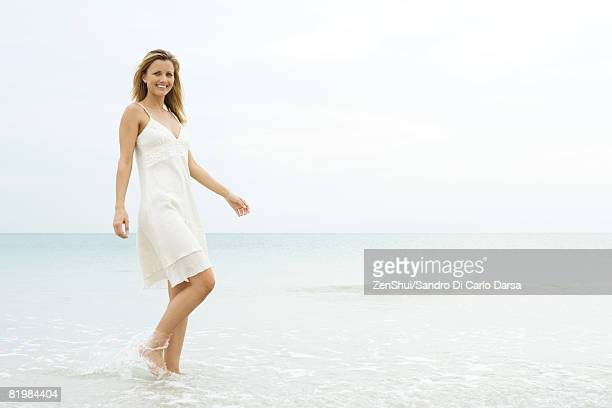 young woman in sundress walking in shallow water, smiling at camera - サンドレス ストックフォトと画像