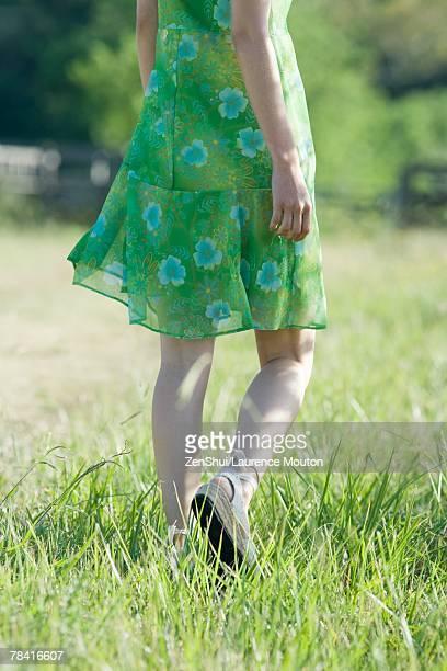 young woman in sundress walking through field - grünes kleid stock-fotos und bilder