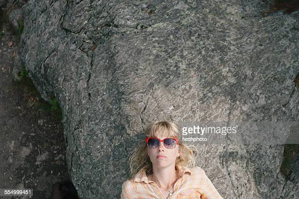 young woman in sunglasses, lying on rock - heshphoto fotografías e imágenes de stock