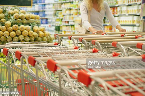 Young woman in supermarket selecting trolley, mid section