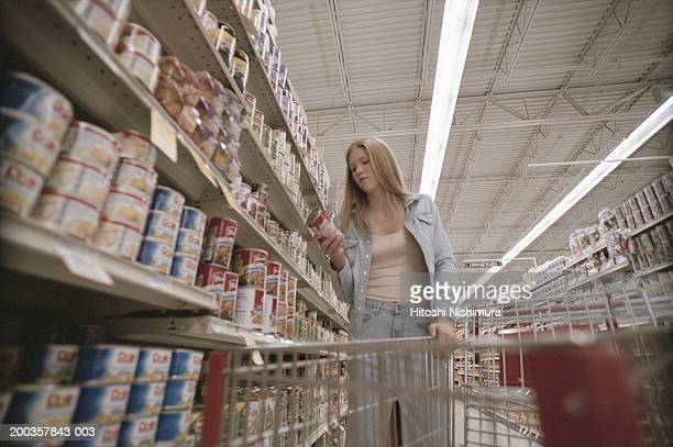Young woman in supermarket with shopping cart, low angle view