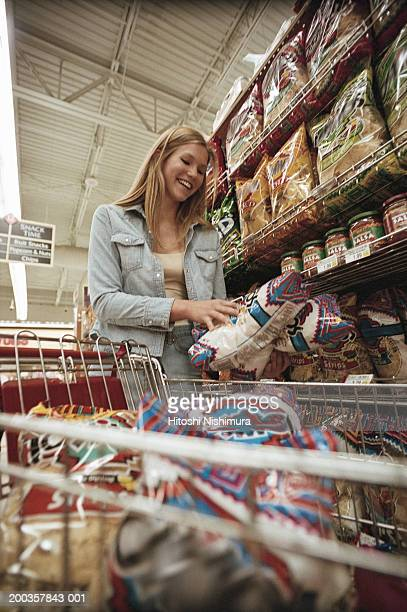 Young woman in supermarket with shopping cart, smiling, low angle view