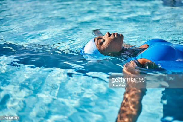 young woman in swimming pool - femme dans son bain photos et images de collection