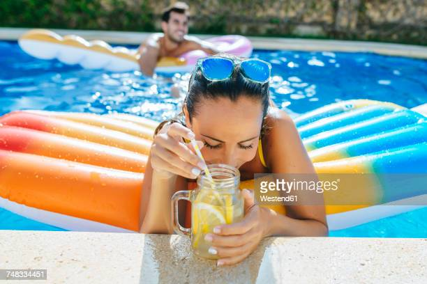 young woman in swimming pool with drink at the poolside - getränk stock-fotos und bilder