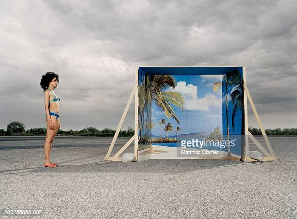 Young woman in swimsuit standing near backdrop, side view