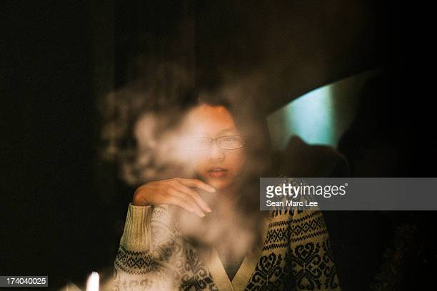 Young woman in Taipei, Taiwan sits at a dinner table contemplating thought with her hand close to her lips. The steam from a hot pot mysteriously...