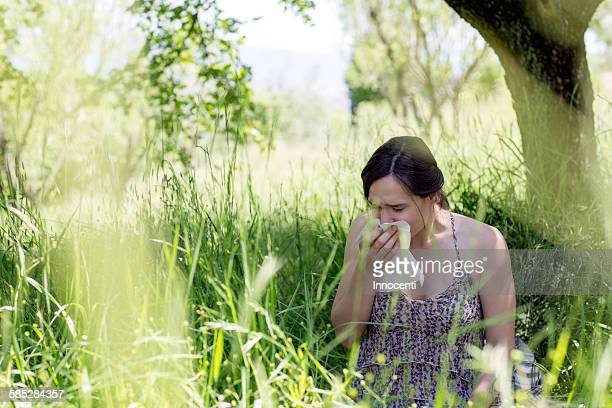 Young woman in tall grass sneezing into handkerchief
