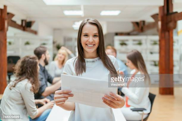 young woman in team meeting holding construction plan
