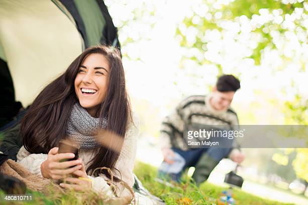 Young woman in tent using smartphone, laughing