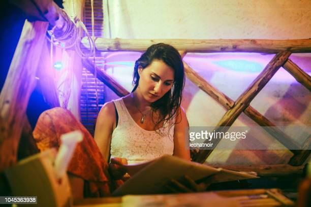 junge frau im thai-restaurant, blick auf die speisekarte - railay strand stock-fotos und bilder