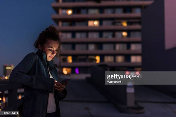 young woman in the city checking cell phone in the evening - portable information device stock-fotos und bilder