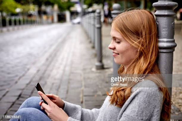 young woman in the city sitting down leaning against a pole using cell phone - dialing stock pictures, royalty-free photos & images